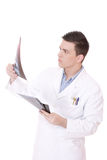 Caucasian mid adult male doctor holding up xrays. Royalty Free Stock Photography