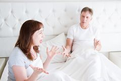 Caucasian middle age family couple angry shouting in bed. Conflict relationship concept. Husband and wife dialogue. Selective royalty free stock photo