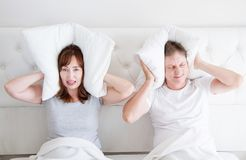 Caucasian middle age family couple in bed. Conflict relationship concept. Husband and wife cover ears by pillow. Selective focus royalty free stock image