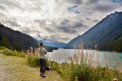 Woman and her Boston Terrier Dog visit River Valley in Pemberton Valley and Duffy Lake Road near Whistler, BC Canada as the Autumn. Caucasian Middle-Aged Woman Royalty Free Stock Photo