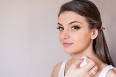 Caucasian model close-up looking straight and smiling during make-up session. The make-up artist is applying the foundation on th royalty free stock photos