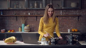 Caucasian model cooking dinner use pc in kitchen. stock video