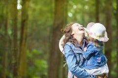 Caucasian moder med hennes lilla dotter som tillsammans poserar i grön sommarskog arkivfoton