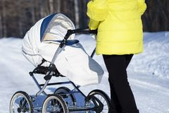 Caucasian mom in yellow coat is walking with white baby carriage on snow road among the forest at winter sunny day Stock Image
