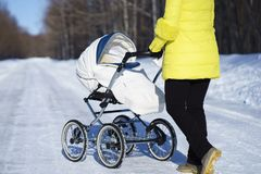 Caucasian mom in yellow coat is walking with white baby carriage on snow road among the forest at winter sunny day Royalty Free Stock Images
