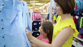 Caucasian mother and daughter near shop shelves choosing shirts in market stock video