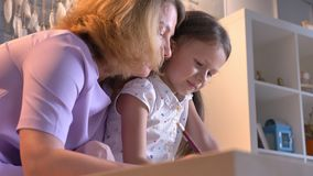 Caucasian mother doing homework with her daughter, helping kid with study, sitting at modern home, family concept stock video