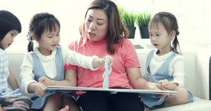 A caucasian mother and her children watch funny cartoons on cartoon book. While together at home. Mother, Daughter and friend quality time. Family time. relax stock video