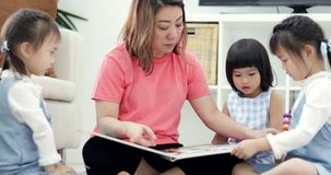 A caucasian mother and her children watch funny cartoons on cartoon book while together at home. Mother, Daughter and friend quality time. Family time. relax stock video