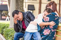 Caucasian Mother and Hispanic Father Comforting Mixed Race Son. Outdoors royalty free stock images