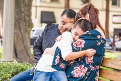 Caucasian Mother and Hispanic Father Comforting Mixed Race Son Outdoors. Caucasian Mother and Hispanic Father Comforting Their Mixed Race Son Outdoors royalty free stock photography