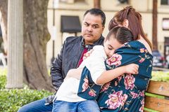 Upset Caucasian Mother and Hispanic Father Comforting Mixed Race Son. Caucasian Mother and Hispanic Father Comforting Mixed Race Son Outdoors stock image