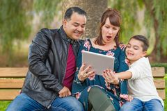Caucasian Mother and Hispanic Father Using Computer Tablet With Mixed Race Son Outdoors. Caucasian Mother and Hispanic Father Using Computer Tablet With Their stock photography