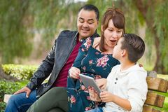Caucasian Mother and Hispanic Father Using Computer Tablet With Mixed Race Son Outdoors. Caucasian Mother and Hispanic Father Using Computer Tablet With Their stock photos