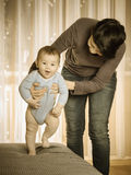Caucasian mother teaching her baby boy to walk. At home Royalty Free Stock Photo