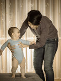 Caucasian mother teaching her baby boy to walk Stock Images