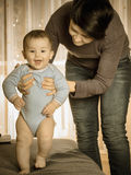 Caucasian mother teaching her baby boy to walk. At home Royalty Free Stock Photography