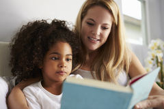 Caucasian mum and black daughter read book in bed, close-up Royalty Free Stock Images