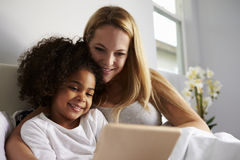 Caucasian mum and black daughter use tablet in bed, close-up Royalty Free Stock Image