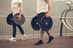Caucasian muscular men with weight plates preparing to outdoor workout. Weightlifting training preparation, close up royalty free stock photos