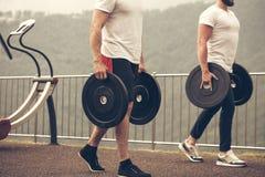 Caucasian muskulösa män med vikt pläterar att förbereda sig till den utomhus- genomköraren royaltyfri bild