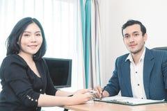 Caucasian och asiatiskt le för affärspartner arkivfoto