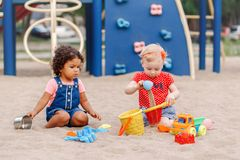 Caucasian och latinamerikansk latin behandla som ett barn barn som sitter, i att spela för sandlåda royaltyfria foton