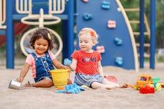 Caucasian och latinamerikansk latin behandla som ett barn barn som sitter, i att spela för sandlåda royaltyfri bild