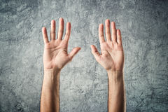 Caucasian Open hands raised. Caucasian male open hands raised as surrender gesture on grunge background Royalty Free Stock Images