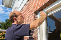 Caucasian Painter Cleaning Window Frame With Cloth Stock Photo