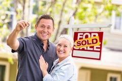 Caucasian par framme av Sold Real Estate tecken- och husintelligens fotografering för bildbyråer