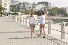 Caucasian par som går på promenaden på sjösidan royaltyfria foton