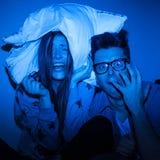 Caucasian par som håller ögonen på läskig film Arkivfoton