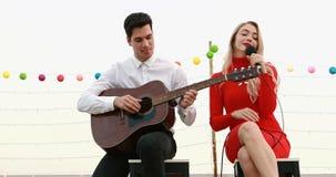 Caucasian par som spelar gitarren och sjunger en sång stock video