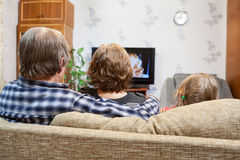 Caucasian parents and daughter sitting on couch and watching tv, rear view stock images