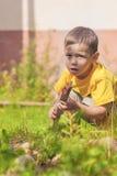 Caucasian pensativo Little Boy que faz o fogo no Firepace Outd Imagens de Stock Royalty Free
