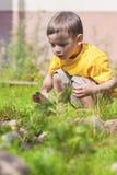 Caucasian pensativo Little Boy que faz o fogo no Firepace Outd Fotos de Stock