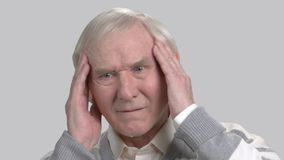 Caucasian pensioner feeling pain in his temples. Old european man suffering from terrible headache, grey background. Pain and facial expression stock video footage