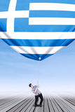 Caucasian person bring down a greece flag Royalty Free Stock Photos