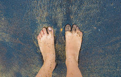 Caucasian person feet foot standing on black volcanic sandy beach Stock Image