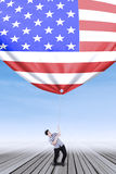 Caucasian person pulling down american flag Stock Image