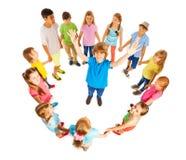 Caucasian pojke i cirkel av vänner Arkivbild