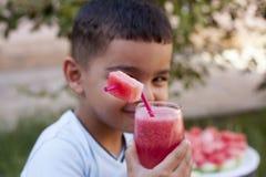 Caucasian pojke med vattenmelonfruktsaft royaltyfria bilder