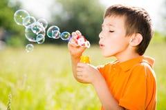 Caucasian pojke som blåser såpbubblorna på naturen royaltyfri foto