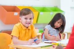 Caucasian pojkeetnicitetunge som ler vit som lär i klassrum royaltyfria bilder