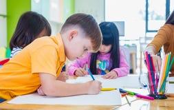 Caucasian pojkeetnicitetunge som ler vitt lära i klassrum med vänner och läraren i dagisskola, utbildning arkivfoton