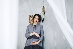 Caucasian pregnant woman with make up in gray dress hugs her belly with owl sitting on her arm, portrait of future. Mother, happy pregnancy, fasion portrait Royalty Free Stock Photos