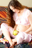 Caucasian pregnant  woman in pink lingerie on bed Royalty Free Stock Image