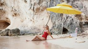 Caucasian pregnant woman relaxing on vacation on a sandy beach beach accessories. Sun umbrella picnic beach accessories. A caucasian pregnant woman smiles and stock video footage