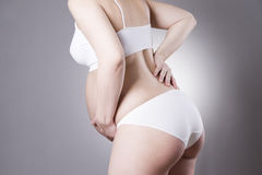 Caucasian pregnant woman in white lingerie with abdominal pain on gray studio background Stock Photo